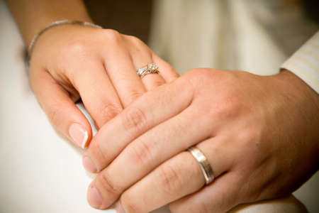 married together: bride and groom holding hands with wedding rings on it Stock Photo