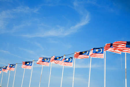 row of Malaysian flags waving outdoor in the field