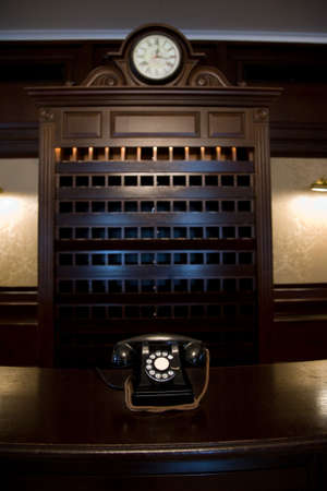 old vintage hotel lobby desk with telephone and clock and key shelf