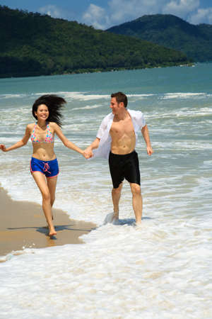 Couple running on beach holding hands smiling photo