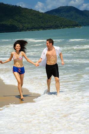 Couple running on beach holding hands smiling Standard-Bild