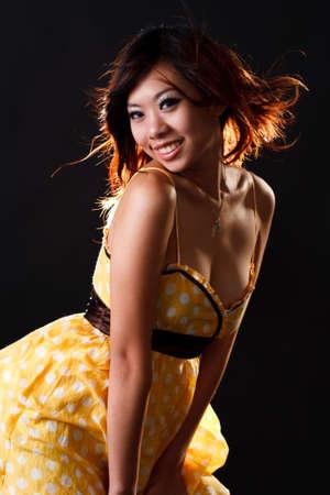 Pretty asian girl ina sexy yelloploka dot dress Stock Photo
