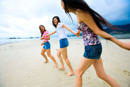 group of asian multi racial girls having fun at the beach Stock Photo