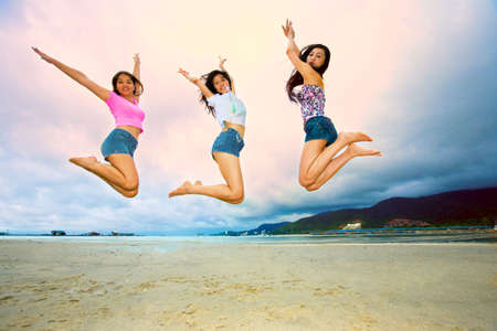 group of happy asian woman jumping up high at the beach