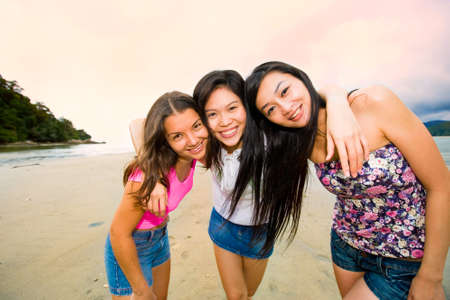 group of happy asian woman friends at the beach