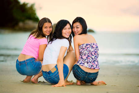 group of happy asian woman friends squatting by the sunset beach
