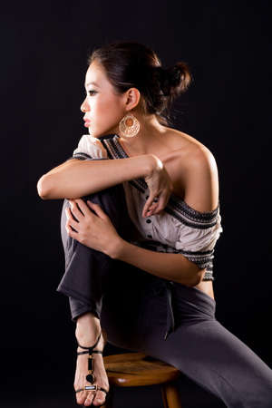 asian fashion beauty sitting on a stool with one up