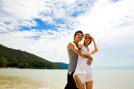 happy asian young couple hugging at the beach enjoyng the view Stock Photo