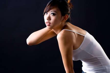 bending down: beautiful asian young woman bending down in casual wear Stock Photo