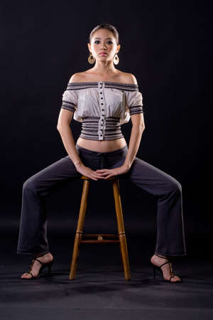seducrive woman sitting with legs wide apart Stock Photo - 4136935
