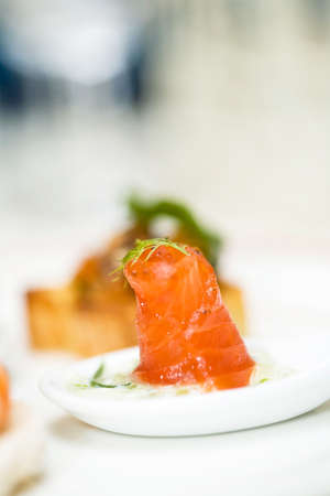 a raw salmon finger food appertizer is served photo
