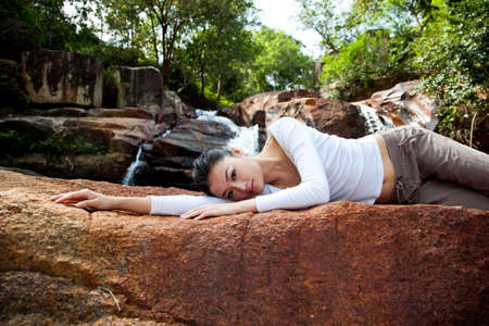 outdoor waterfall young woman relaxing on the rock photo