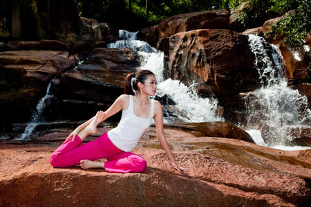 outdoor young woman sitting by the waterfall doing yoga