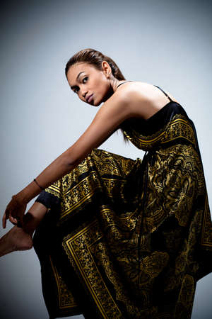 artistic pose of young woman in golden floral batik dress