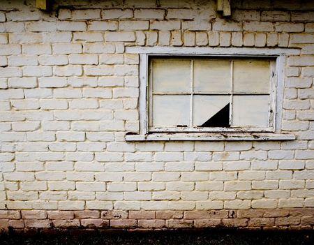 Broken window pane on derelict building wall photo