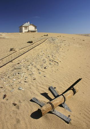 encroaching: Abandoned house in encroaching desert with dilapidated signpost and railway tracks
