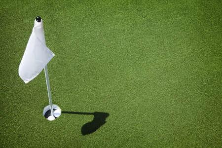 Twee golfballen zitten in beker op golfbaan putting green met vlag. Stockfoto