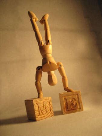 Wooden mannequin Standing on wooden M and E blocks. Banco de Imagens