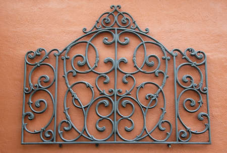 A Decorative Piece of Wrought Iron Mounted to a Bright Colored Stucco Wall