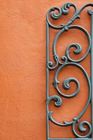 Decorative Wrought Iron Mounted to a Bright Colored Stucco Wall