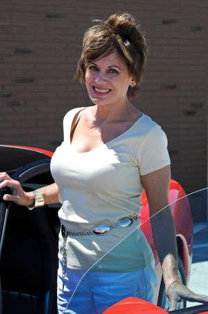 魅力的な女性は彼女赤のスポーツ車 写真素材