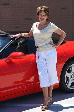 매력적인 여자와 그녀의 빨간 스포츠카