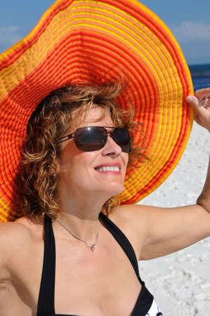 魅力的な女性は明るい夏帽子をかぶっています。 写真素材
