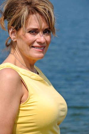 湖のそばの魅力的な成熟した女性 写真素材