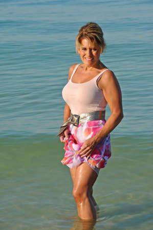 魅力的な成熟した女性は海で水遊び 写真素材