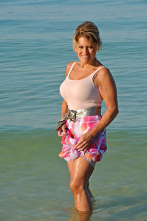 바다에서 매력적인 성숙한 여자 넘어 가고