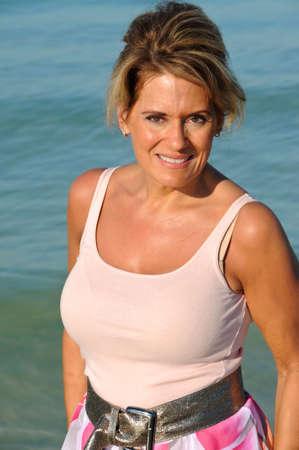 해변에서 이른 아침 태양 즐기기 매력적인 성숙한여 인