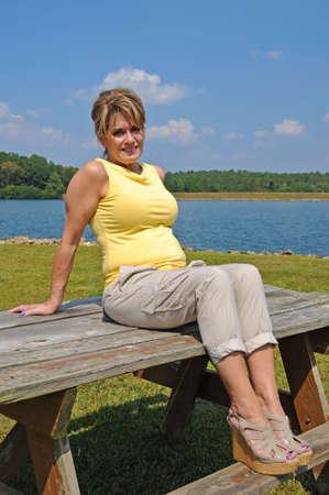 湖のほとりにピクニック テーブルの上に座っている魅力的な女性