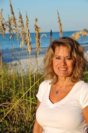 해변에서 이른 아침 태양을 즐기는 매력적인 여자
