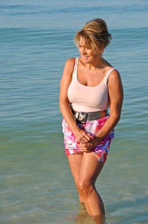 サーフィンでウェーディング魅力的な成熟した女性 写真素材