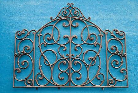 明るい色の漆喰壁にマウントされている錬鉄の装飾的な作品