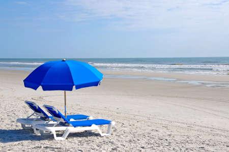 Twee strandstoelen met blauwe parasol op het strand Stockfoto