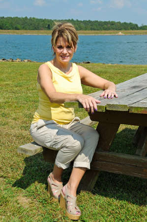 Pretty Woman Seating at Picnic Table on the Lake Foto de archivo