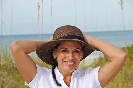 해변에 태양 모자를 입고 서있는 매력적인 여자