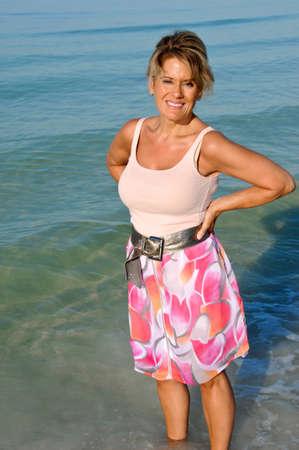 魅力的な女性は海の波に立っています。