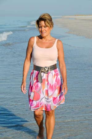 매력적인 여자는 여름 복장으로 해변에 산책
