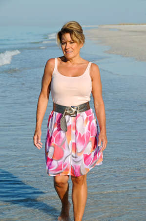 Attractive Woman Walking on the Beach in a Summer Dress Stock Photo