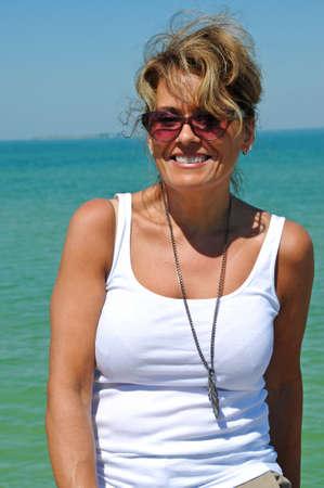 魅力的な女性は浜の遊歩道沿いに座っています。