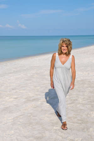 Attractive Woman Walking on the Beach in a Sundress
