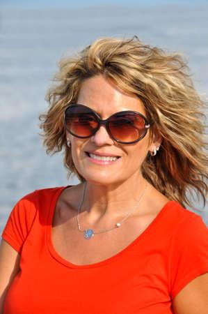赤いシャツを着て、魅力的な中年女性の屋外のポートレート