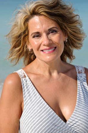 サンドレスでビーチに魅力的な中年女性