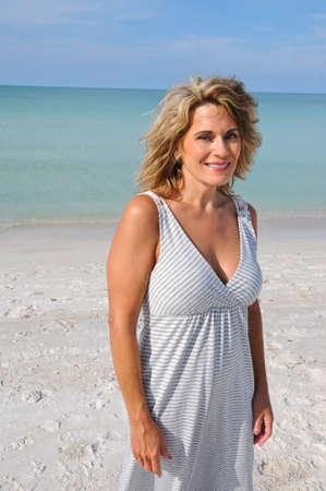 Portret van middelbare leeftijd vrouw draagt een zon jurk op het strand Stockfoto