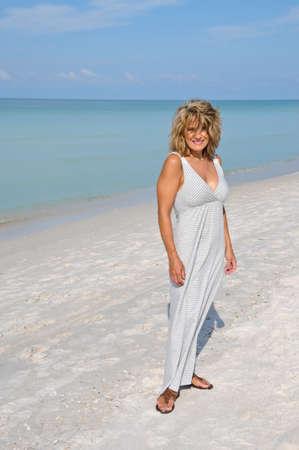 Aantrekkelijke Vrouw wandelen op het strand in een Sundress