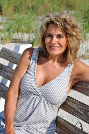 Aantrekkelijke Vrouw zittend op een bankje op het strand Stockfoto