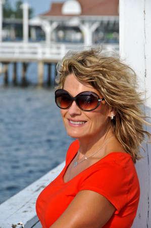 魅力的な笑みを浮かべて中年女性を身に着けてレッド トップにもたれて手すり、バック グラウンドで海と