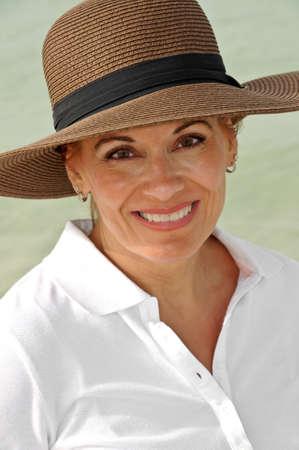 魅力的な女性は茶色の夏帽子を身に着けている白のトップに 写真素材